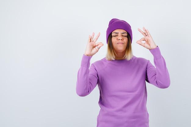Junge dame, die meditationsgeste in lila pullover, mütze zeigt und friedlich aussieht, vorderansicht.