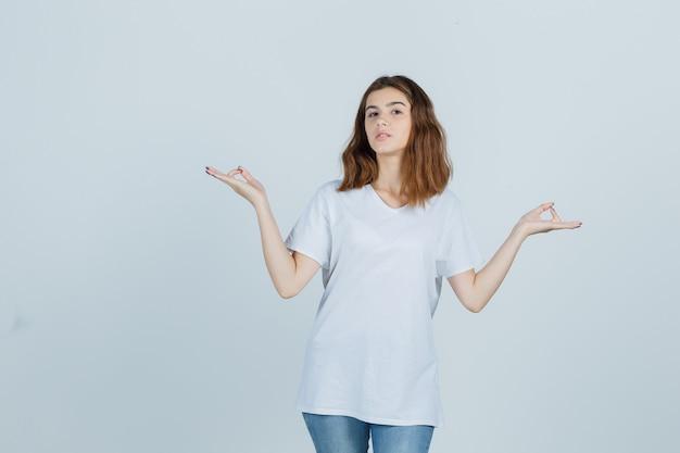Junge dame, die meditationsgeste in t-shirt, jeans zeigt und friedlich, vorderansicht schaut.