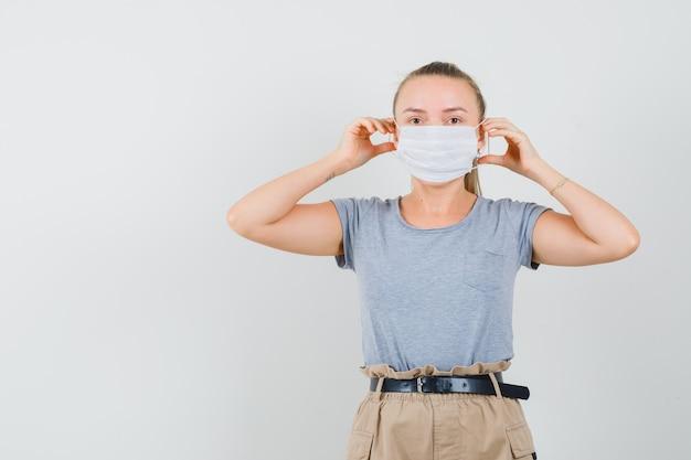 Junge dame, die medizinische maske im t-shirt und in der hose trägt und vorsichtig schaut