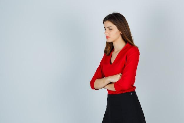 Junge dame, die mit verschränkten armen steht, während weg in der roten bluse schaut