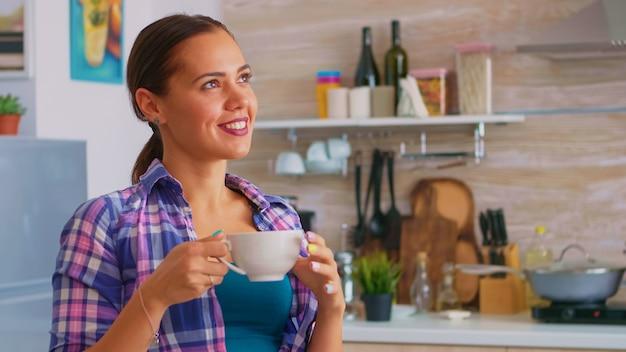 Junge dame, die morgens mit grünem tee in der küche sitzt. verträumte glückliche frau, die wegschaut, morgens kräutertee zu hause trinkt, lächelt und eine tasse hält, die mit angenehmen erinnerungen genießt