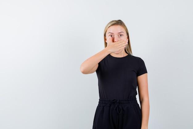 Junge dame, die mund mit hand in t-shirt, hose bedeckt und ängstlich aussieht. vorderansicht.