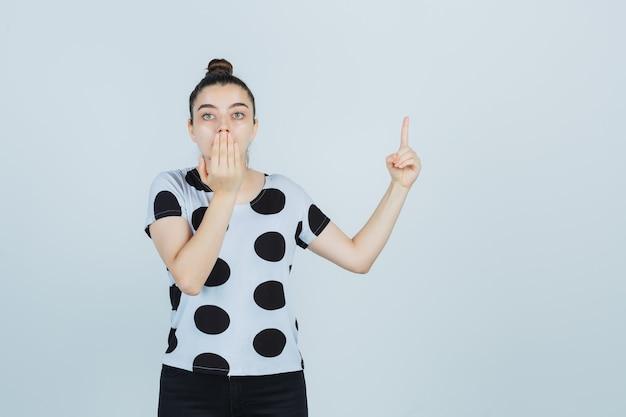 Junge dame, die nach oben zeigt, während mund mit hand in t-shirt, jeans bedeckt und verwirrt aussieht. vorderansicht.