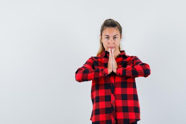Junge dame, die namaste geste im karierten hemd zeigt und selbstbewusst aussieht