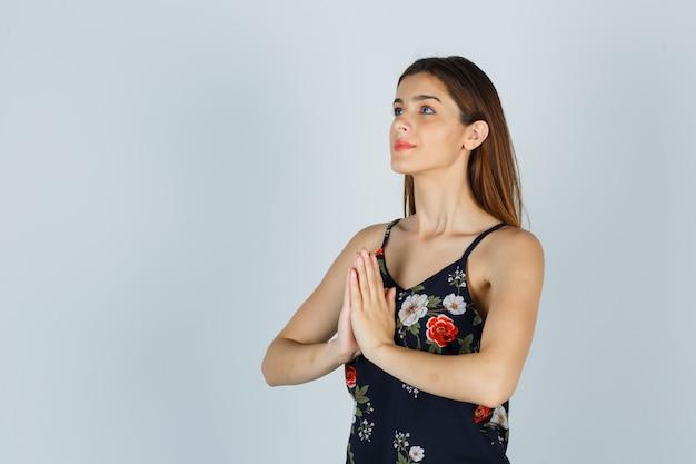 Junge dame, die namaste-geste in bluse zeigt und friedlich aussieht. vorderansicht.