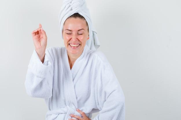 Junge dame, die oben zeigt, während hand auf taille im weißen bademantel, handtuch hält und glücklich schaut, vorderansicht.