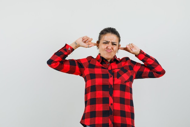 Junge dame, die ohren mit den fingern im karierten hemd verstopft und genervt aussieht.