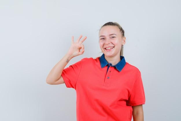 Junge dame, die ok geste im t-shirt zeigt und fröhlich aussieht