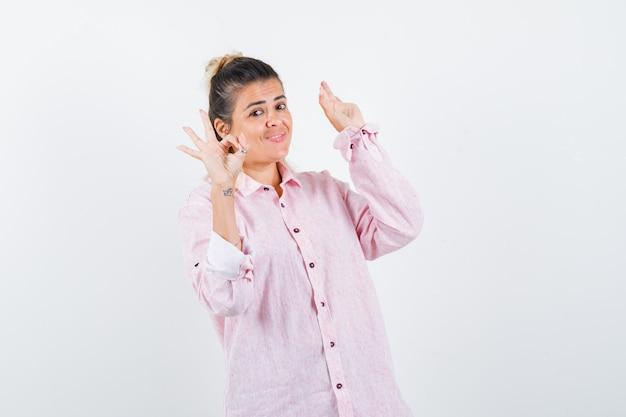 Junge dame, die ok geste zeigt, offene hand im rosa hemd erhebt und fröhlich aussieht