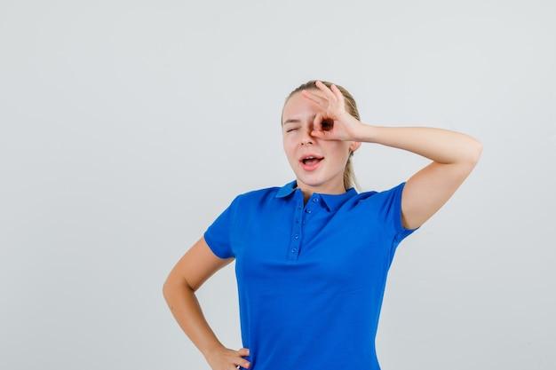 Junge dame, die ok zeichen auf auge zeigt, während sie im blauen t-shirt zwinkert