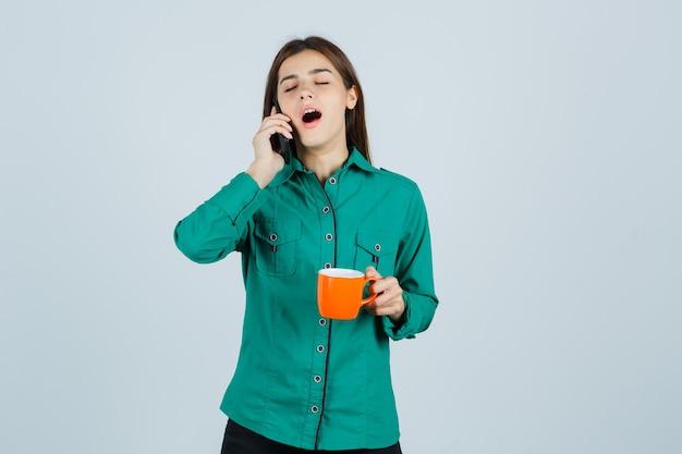 Junge dame, die orange tasse tee hält, auf dem handy im hemd spricht und schläfrig sieht, vorderansicht.