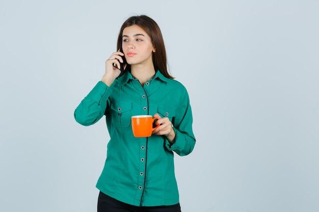 Junge dame, die orange tasse tee hält, auf dem handy im hemd spricht und zuversichtlich schaut. vorderansicht.