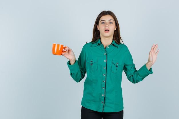Junge dame, die orange tasse tee hält, hand im hemd hebt und ratlos aussieht. vorderansicht.
