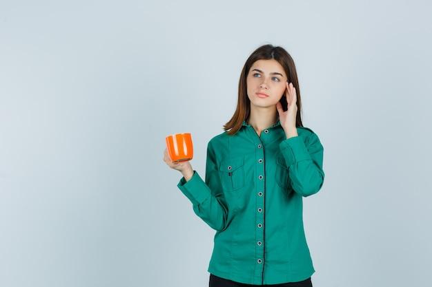 Junge dame, die orange tasse tee hält, hand nahe gesicht im hemd erhebt und nachdenklich schaut. vorderansicht.