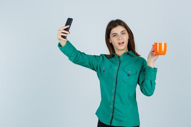 Junge dame, die orange tasse tee hält, selfie mit handy im hemd nimmt und zuversichtlich, vorderansicht schaut.