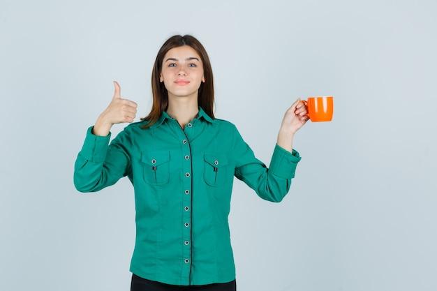 Junge dame, die orange tasse tee hält, während daumen oben im hemd zeigt und erfreut aussieht. vorderansicht.
