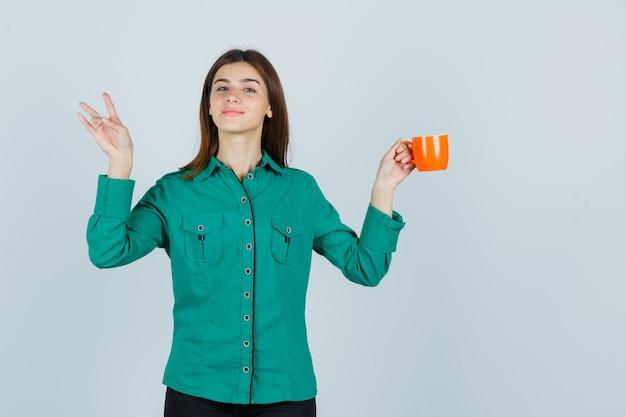 Junge dame, die orange tasse tee hält, während nummer drei im hemd zeigt und erfreut, vorderansicht schaut.
