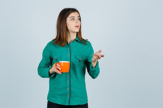 Junge dame, die orange tasse tee im hemd hält und fokussierte vorderansicht schaut.