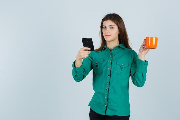 Junge dame, die orange tasse tee und handy im hemd hält und zuversichtlich, vorderansicht schaut.