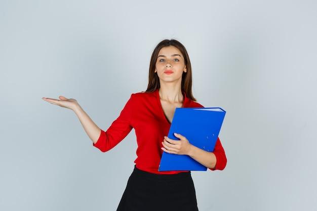 Junge dame, die ordner hält, während sie etwas in der roten bluse zeigt