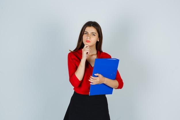 Junge dame, die ordner hält, während sie in der denkenden haltung in der roten bluse steht