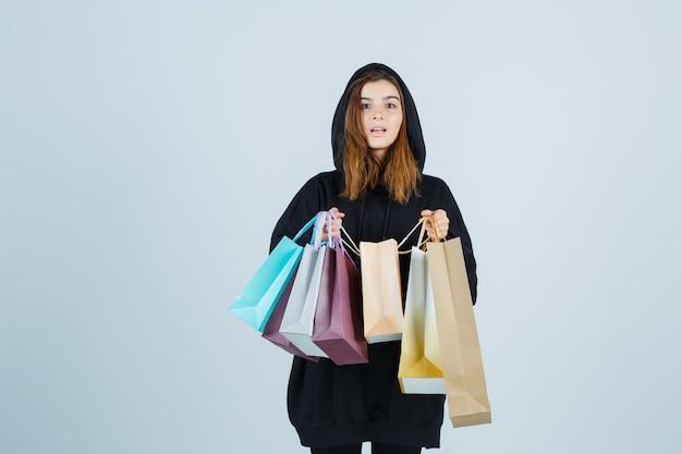 Junge dame, die pakete hält, während sie kamera in übergroßem kapuzenpulli, hosen betrachtet und erstaunt, vorderansicht schaut.
