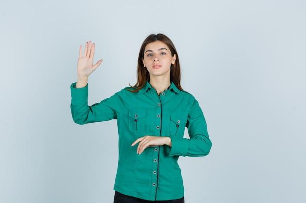 Junge dame, die palme im grünen hemd zeigt und zuversichtlich, vorderansicht schaut.