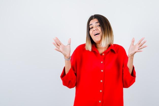 Junge dame, die palme zeigt, während sie in rotem übergroßem hemd in die kamera schaut und fröhlich aussieht, vorderansicht.