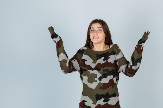 Junge dame, die palmen im pullover beiseite spuckt und vorsichtig schaut