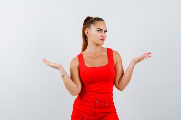 Junge dame, die palmen im roten unterhemd, in der roten hose beiseite spreizt und vorsichtig schaut. vorderansicht.