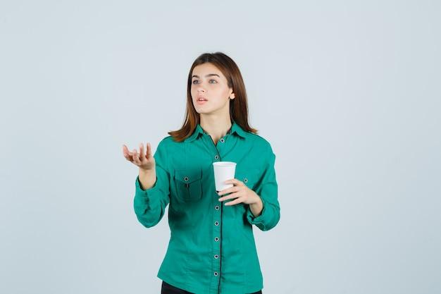 Junge dame, die plastikbecher kaffee hält, hand in fragender weise im hemd streckt und konzentriert schaut. vorderansicht.