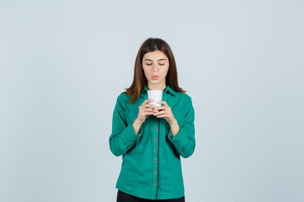 Junge dame, die plastikbecher kaffee im hemd hält und fokussierte vorderansicht schaut.