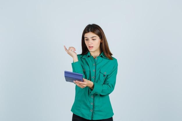 Junge dame, die rechner betrachtet, während eureka-geste im grünen hemd zeigt und überrascht schaut. vorderansicht.