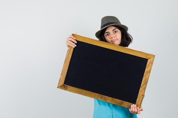 Junge dame, die schwarzen rahmen im blauen hemd, im hut zeigt und selbstbewusst aussieht.