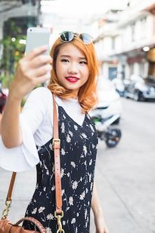 Junge dame, die selfie auf straße nimmt