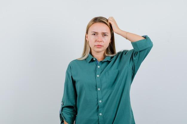 Junge dame, die sich im grünen hemd am kopf kratzt und nachdenklich aussieht