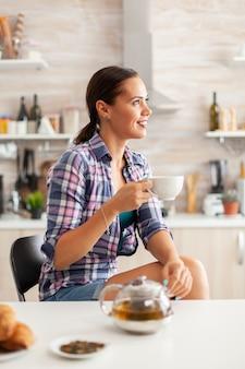 Junge dame, die sich morgens mit grünem tee entspannt, sitzt in der kücheverträumte glückliche frau, die wegschaut, morgens kräutertee zu hause trinkt, lächelt und eine tasse hält, die mit angenehmen erinnerungen genießt