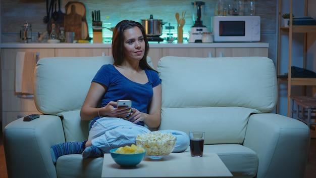 Junge dame, die sich nachts mit dem telefon entspannt und auf dem sofa sitzt. einsame amüsierte glückliche frau liest, schreibt, sucht, surft auf dem smartphone und lacht amüsant mit technologie internet