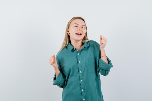 Junge dame, die siegergeste im grünen hemd zeigt und glücklich aussieht