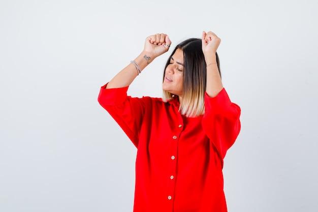 Junge dame, die siegergeste im roten übergroßen hemd zeigt und glücklich schaut, vorderansicht.