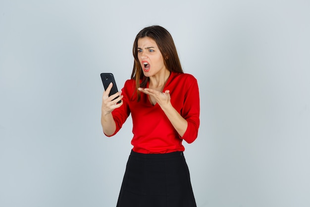 Junge dame, die sprachnachricht auf handy in roter bluse aufzeichnet