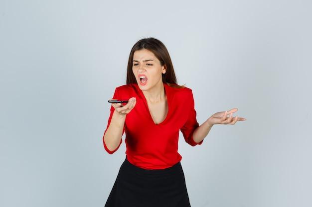 Junge dame, die sprachnachricht auf handy in roter bluse, rock aufzeichnet und wütend schaut