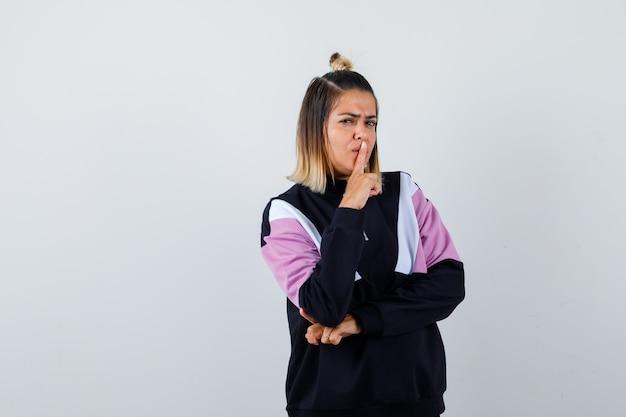 Junge dame, die stille-geste im hoodie-pullover zeigt und ernst aussieht.