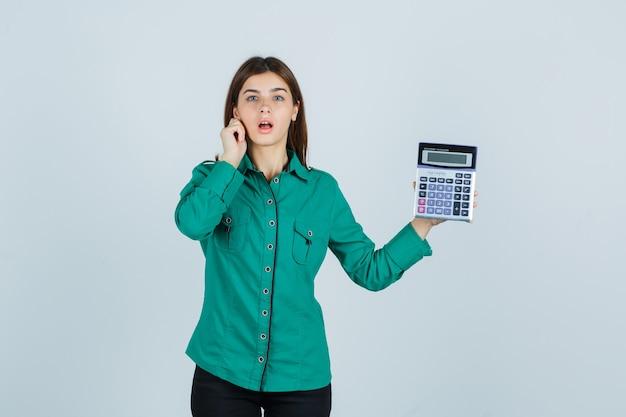 Junge dame, die taschenrechner hält, während sie ihr ohrläppchen im grünen hemd herunterzieht und ängstliche vorderansicht schaut.