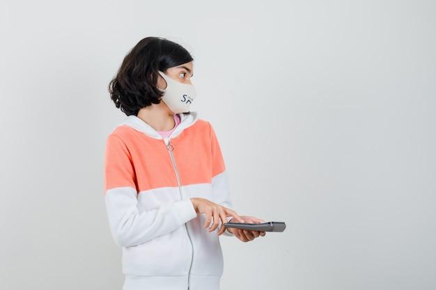 Junge dame, die taschenrechnerknopf im kapuzenpulli, gesichtsmaske drückt und verwirrt schaut