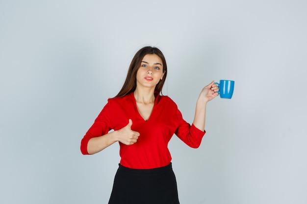 Junge dame, die tasse hält, während daumen oben in roter bluse, rock zeigt und selbstbewusst aussieht