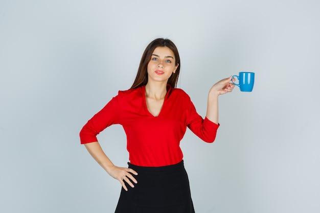 Junge dame, die tasse hält, während hand auf hüfte in roter bluse hält