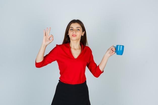 Junge dame, die tasse hält, während sie ok geste in der roten bluse zeigt