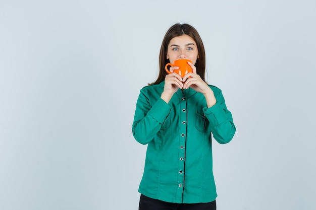 Junge dame, die tee von der orange tasse im hemd trinkt und zuversichtlich schaut. vorderansicht.