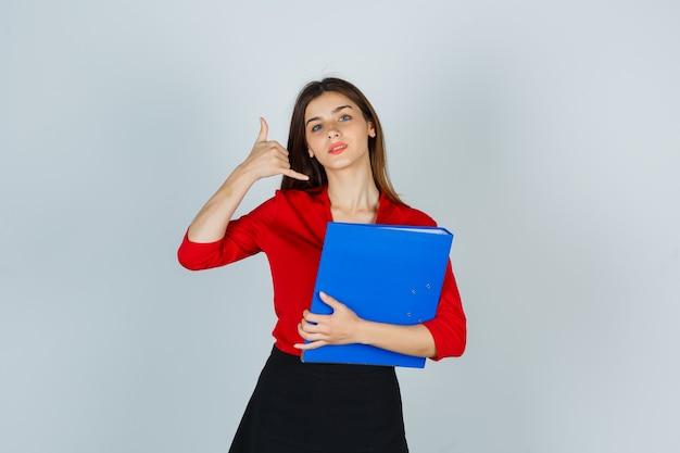 Junge dame, die telefongeste zeigt, während ordner in roter bluse hält